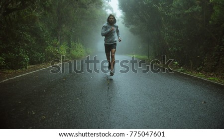 Handsome, young jogger running in the exotic area #775047601