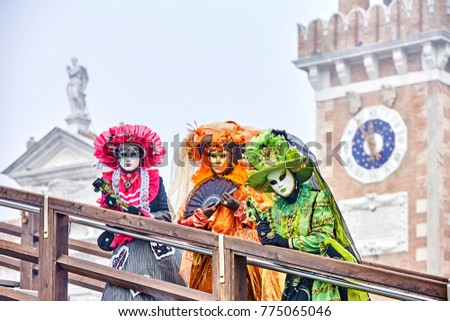 Venetian mask . Carnival mask in Venice, Italy. Carnival Venice 2017. portrait of Costumed woman at the Venetian Parade. Venice Carnaval.  Against the backdrop of the arsenal of venice #775065046