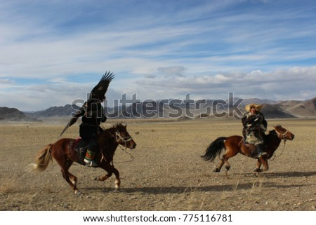 BAYAN-OLGII PROVINCE, MONGOLIA - OCT. 01, 2017: Golden Eagle Festival. Unknown Mongolians horsemen in traditional clothing posing for travelers. #775116781