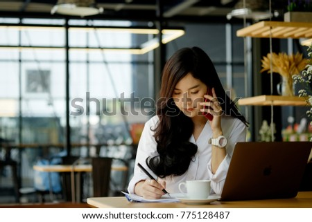 Portrait of an attractive young woman holding her phone while working in coffee shop. #775128487