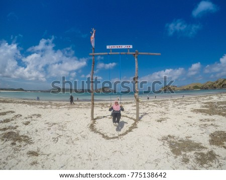 LOMBOK , INDONESIA - May 22, 2017: Unidentified young woman muslim traveller swinging at tropical beach near Kuta, Lombok, Indonesia.  #775138642