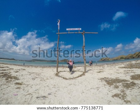 LOMBOK , INDONESIA - May 22, 2017: Unidentified young woman muslim traveller swinging at tropical beach near Kuta, Lombok, Indonesia.  #775138771