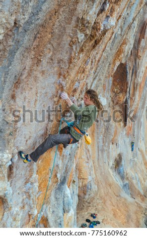 A man climbs the rock alone. A dangerous route. Rock climbing. The beauty of sports. Extreme activity. Red rocks. Rock climbing in Turkey. #775160962