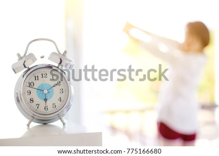 Focus alarm clock morning time with blur a woman stand near the window and sunlight. Adequate sleep and sleep tight concept. image for background, copy space and object.
