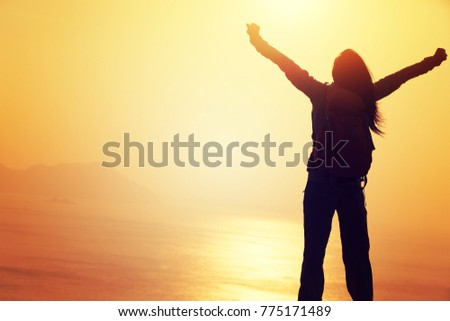 free female hiker with backpack standing on sunrise windy coast #775171489