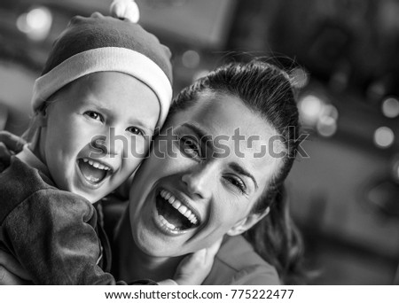 Portrait of smiling mother and baby in christmas decorated kitchen #775222477