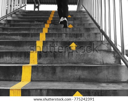 Looking up to people walking on flyover across the street following yellow arrows direction for safety and being in order. Royalty-Free Stock Photo #775242391