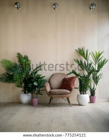 Modern loft living room with plywood wall, wooden floor, retro brown leather armchair with pillow and green tropical fern plants in pots. Mock up interior photo simple urban jungle style #775254121