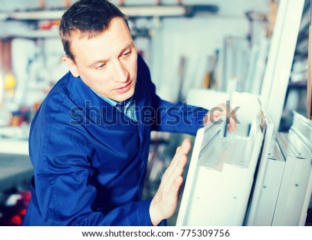 Happy workman inspecting PVC manufacturing output in workshop #775309756