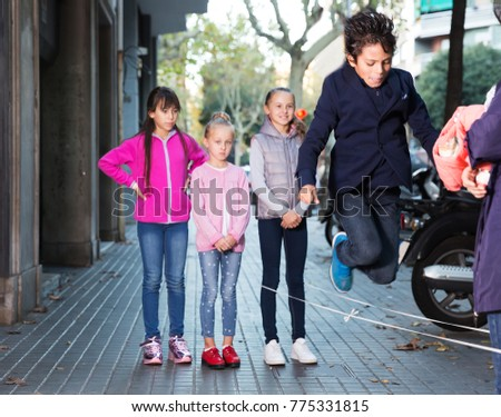 Smiling children play on city sidewalk in autumn city #775331815