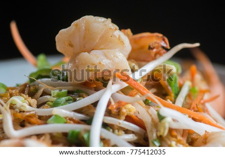 Pad Thai with shrimp, rice noodles, eggs, white radish, sliced carrots, fish sauce, soybeans sprouts with tamarind sauce is shown in a serving bowl. #775412035