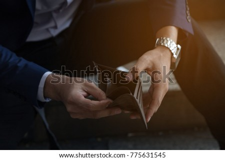 BUSINESSMAN on Have MONEY Unemployed and Bankrupt Looks into his Empty Wallet.  Stress Crisis, Unemployed Businessmen are Waiting for new Jobs,Recession Situation and Hopelessness crisis concept. Royalty-Free Stock Photo #775631545