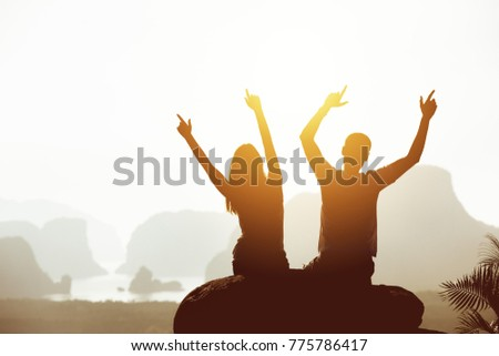 Travel concept with happy couple sitting on big rock with raised arms on mountains and islands backdrop. Place for text #775786417