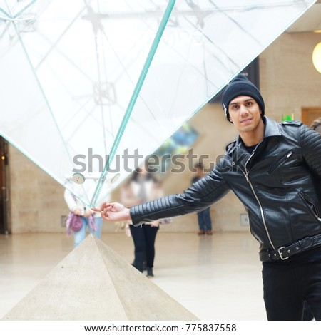 Handsome man in black leather jacket smile for photo with finger at glass reverse pyramid