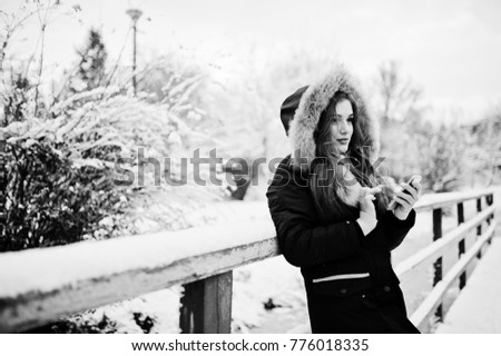 Beautiful brunette girl in winter warm clothing. Model on winter jacket against frozen lake at park speak on mobile phone. #776018335