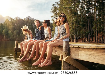 Portrait of happy young woman sitting on the edge of a pier with friends. Group of young friends enjoying a day at the lake. #776026885