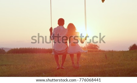 LENS FLARE SILHOUETTE: Unrecognizable couple in love swaying on tree swing at golden summer sunset. Happy man and woman swinging under a tree in sunny evening. Romantic boy and girl embracing on swing #776068441