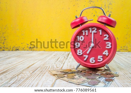 alarm clock and many coins on the wooden texture