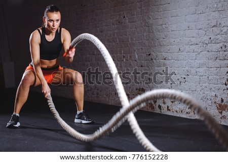 Woman training with battle rope in cross fit gym #776152228