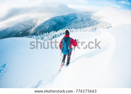 A man in snowshoes in the mountains in the winter. A climber with trekking sticks walks through the snow. Winter ascent. Beautiful sky with clouds. #776173663