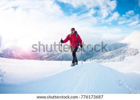 A man in snowshoes in the mountains in the winter. A climber with trekking sticks walks through the snow. Winter ascent. Beautiful sky with clouds. #776173687