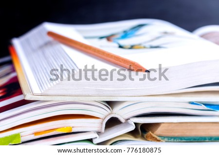 Open hardback and textbook stacked on the table on blackboard background. The concept of intelligence comes from education. focused on the textbook. #776180875