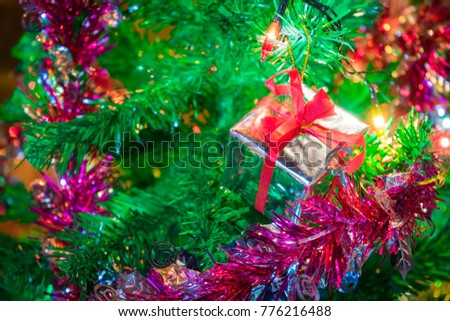 Close up of decorated Christmas tree with colorful lighting and present box. #776216488