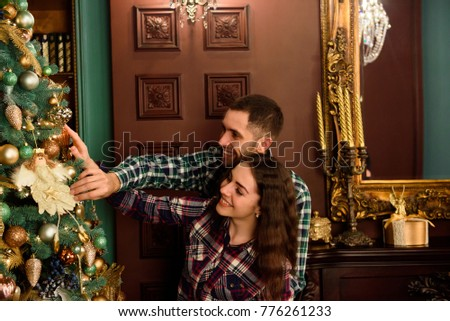 Couple in love next to a Christmas tree, hugging and looking awa #776261233