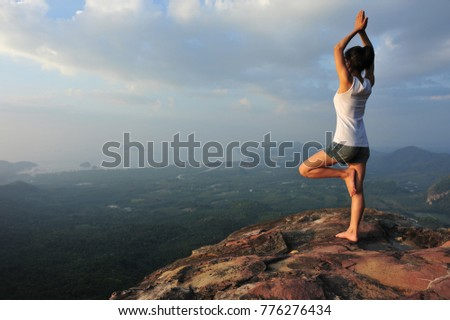 one woman practicing yoga at mountain peak cliff edge #776276434