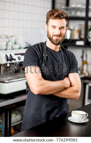 Portrait of a handsome barista in black t-shirt and apron standing at the bar of the modern cafe #776299081