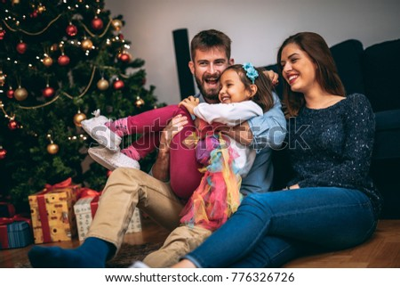 Young family having fun in front of the Christmas tree. #776326726