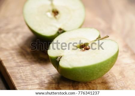 green apple on wood board closeup #776341237