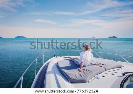 beautiful woman enjoying luxurious yacht cruise, sea travel by luxury boat Royalty-Free Stock Photo #776392324