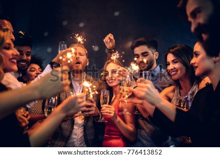 Group of people celebrating with champagne and sparklers #776413852