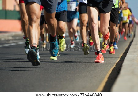 Marathon running in the light of evening,running on city road detail on legs Royalty-Free Stock Photo #776440840