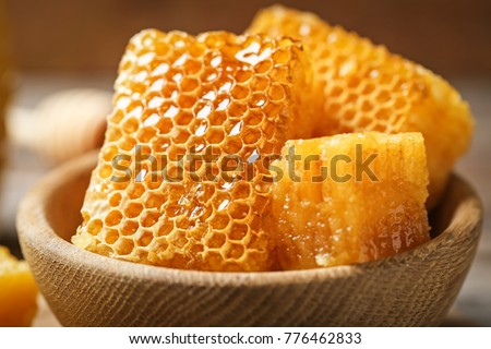 Fresh honeycombs in wooden bowl, closeup Royalty-Free Stock Photo #776462833