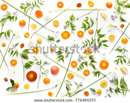 Pattern of of flowers and fruits. Abstract food background, top view, flat lay. Composition of  flowers, tangerines, persimmons, isolated on a white background. Healthy eating. Summer, spring concept.