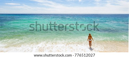 Woman and sea. Girl in white swimwear standing on the beach. Back view. Panorama.