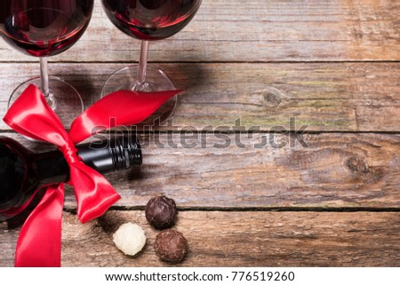 A dark bottle of wine with a red bow, glasses of wine and chocolate truffles.Top view #776519260