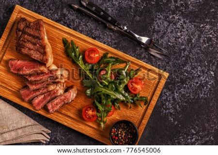 Beef steak on a dark background. Top view, copy space. #776545006