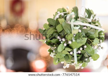 mistletoe hanging in house with fireplace and bokeh Christmas lights blurred in background
