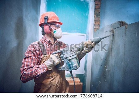 builder with hammer breaking wall indoors #776608714