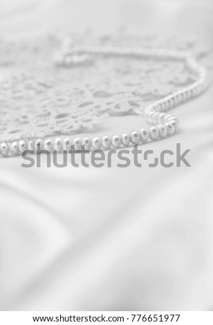Smooth elegant white silk or satin with pearls and lace can use as wedding retro background. In black and white toned. Retro style #776651977