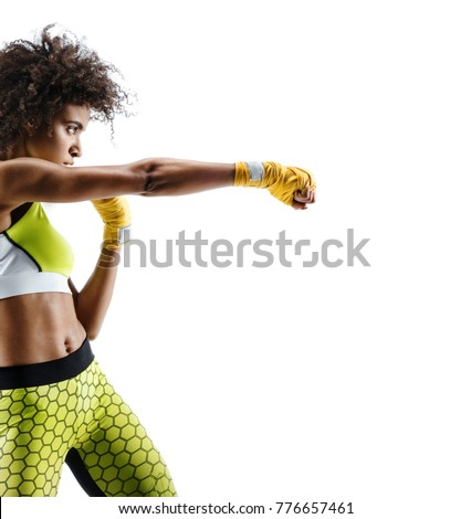 Boxer woman in yellow bandages making direct hit. Photo of sporty african woman during boxing on white background. Dynamic movement. Side view #776657461