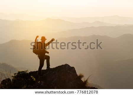 Silhouette of man hold up hands on the peak of mountain,success concept #776812078
