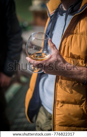 a glass full of cognac is held by a man #776822317