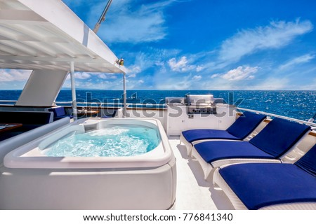 Sunny aft deck of a large, luxurious private motor yacht featuring a hot tub spa, deck chairs, and a barbecue. Blue skies and tropical water add to the concept of living the good life. #776841340