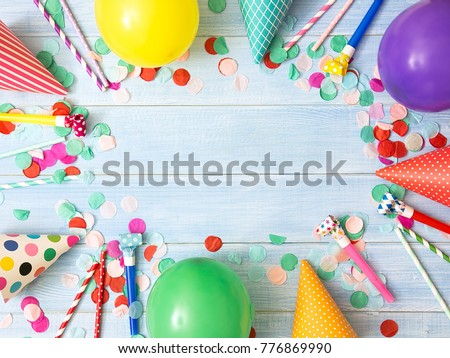Frame or background with colorful balloon, confetti, carnival cap and streamer. Flat lay style. Used for birthday or party greeting card with center copy space.