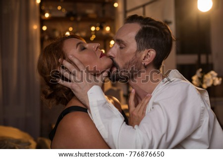 Profile of passionate bearded man kissing woman with desire while touching her face gently. Female eyes are closed with pleasure. Closeness concept #776876650