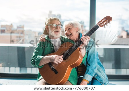 Musical holiday. Waist up portrait of amorous married man and woman enjoying playing on instrument #776880787